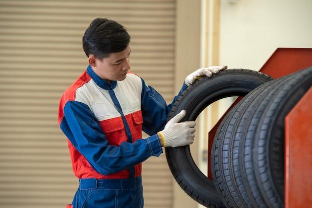 Mecânico que guarda um pneu na garagem do reparo, mecânico do pneu com conceito dos pneus.