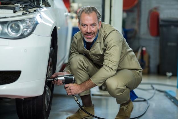 Mecânico que repara uma roda de carro com chave pneumática