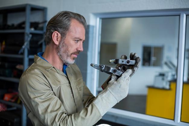 Mecânico que verific um carro peças