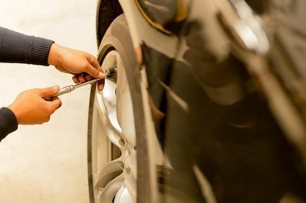 Mecânico que verifica a pressão de ar e que enche o ar nos pneus.