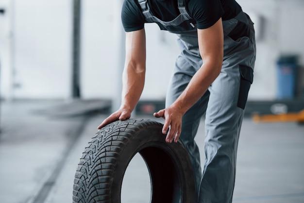 Mecânico segura um pneu na oficina