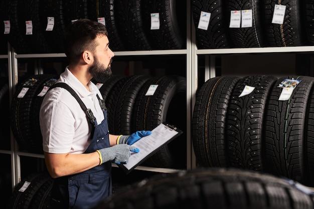 Mecânico segurando um documento de tablet de papel nas mãos enquanto verifica o sortimento no serviço de reparo de automóveis, mecânico especializado trabalhando sozinho na oficina mecânica, atende os clientes