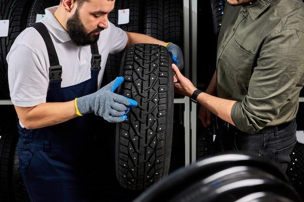Mecânico segurando um pneu e mostrando os pneus da roda em uma oficina mecânica e loja de automóveis, jovem barbudo homem uniformizado trabalhando na oficina mecânica
