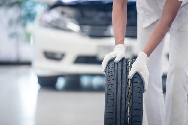 Mecânico segurando um pneu na garagem de reparação. substituição de pneus de inverno e verão.