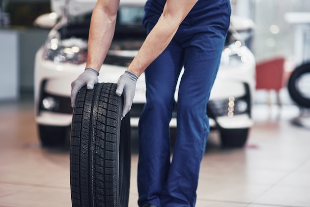 Mecânico segurando um pneu na garagem de reparação. substituição de pneus de inverno e verão