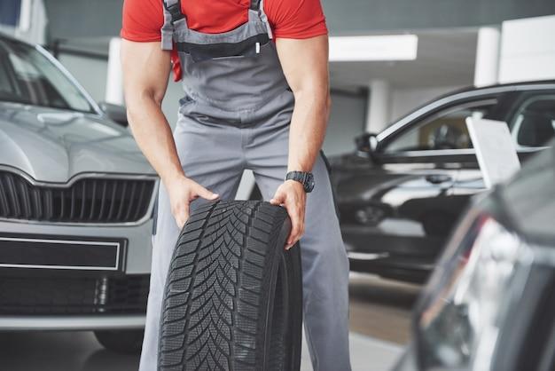 Mecânico segurando um pneu na oficina. substituição de pneus de inverno e verão.