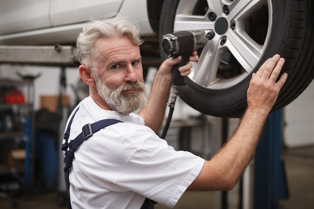 Mecânico sênior de carros barbudo sorrindo para a câmera enquanto trabalhava com a chave de torque na garagem