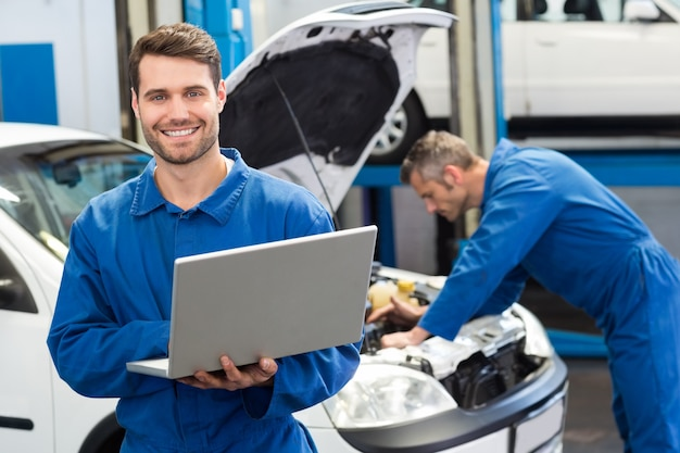 Mecânico sorridente usando um laptop