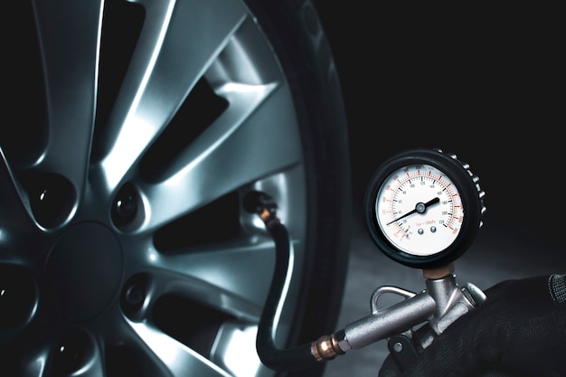 Mecânico testando a pressão do pneu com medidor de pressão do pneu