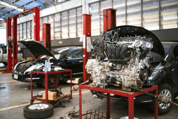 Mecânico trabalhando em manutenção de carro com foco suave e luz de fundo