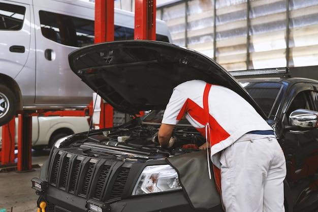 Mecânico trabalhando na manutenção do carro com foco suave e luz de fundo