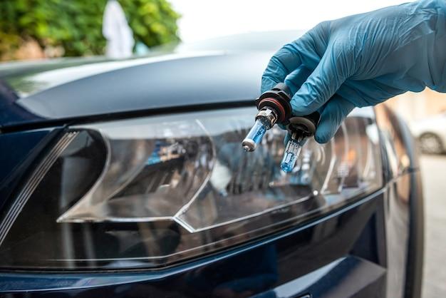 Mecânico trocando a lâmpada do carro contra o farol, serviço automotivo