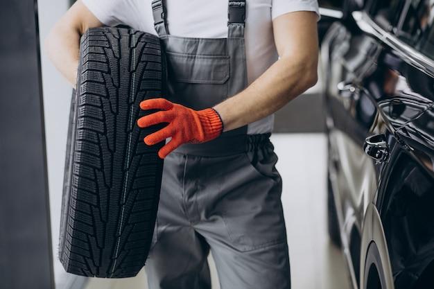 Mecânico trocando pneus em um serviço de automóveis Foto gratuita