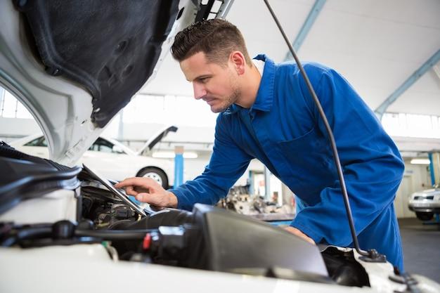Mecânico usando tablet para consertar carro