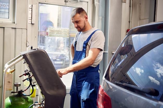 Mecânico verifica o sistema de ar condicionado no serviço automotivo