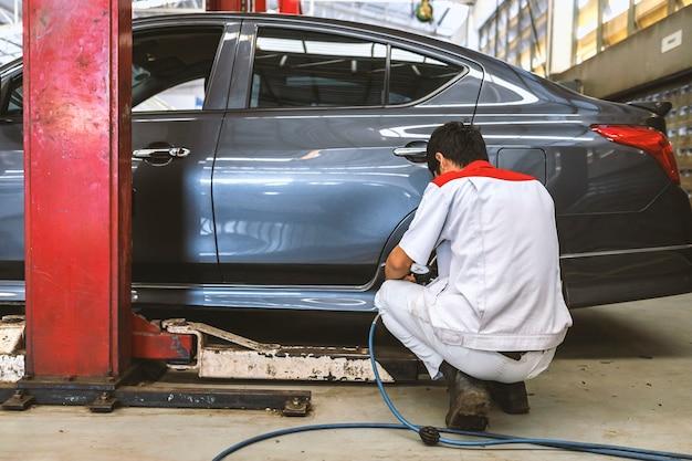 Mecânico verificando a pressão dos pneus no centro de serviço de conserto de automóveis