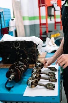 Mecânico verificando peças de automóveis na oficina