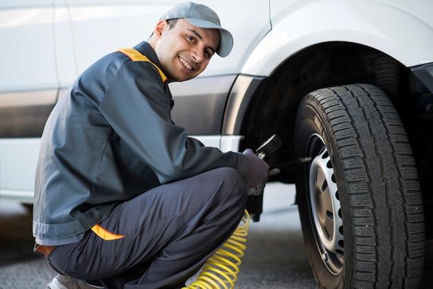 Mecânico verificar a pressão de um pneu de van