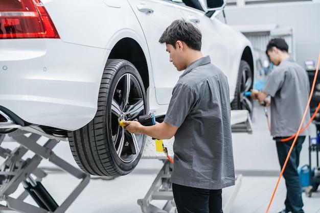 Mecânicos asiáticos que verificam as rodas de carro no centro de serviço de manutenção