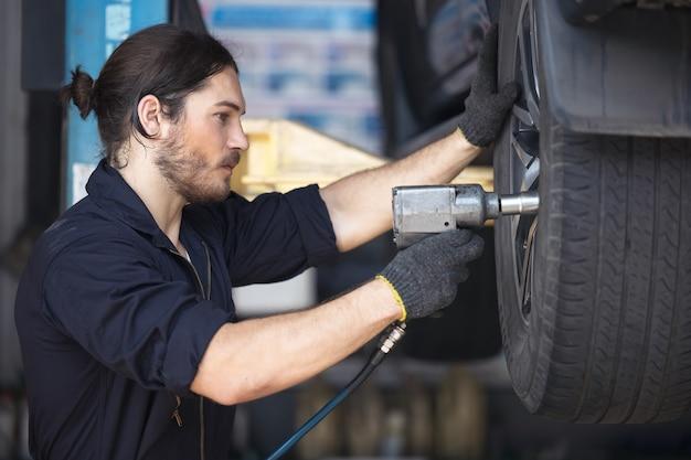Mecânicos consertando pneus de carros na garagem
