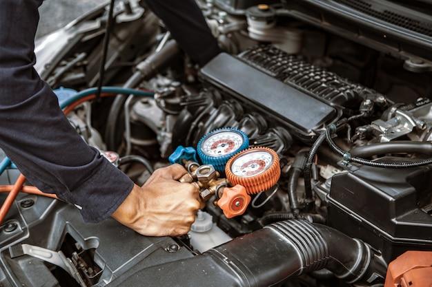 Mecânicos de automóveis estão usando uma ferramenta de equipamento de medição para encher os condicionadores de ar