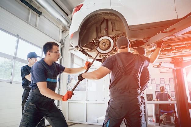 Mecânicos de automóveis reparam suspensão de carro de automóvel levantado na estação de serviço de reparo