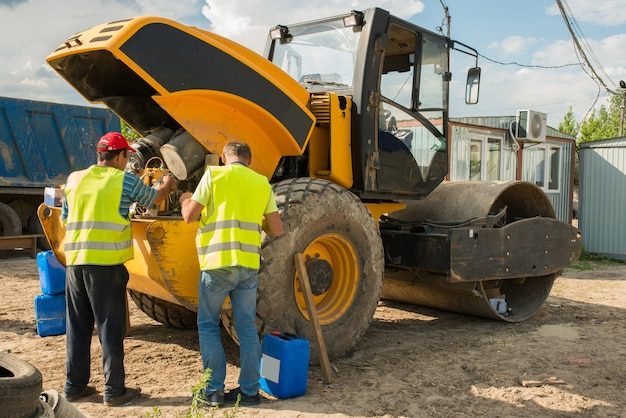 Mecânicos de construção trocam o óleo em um compactador