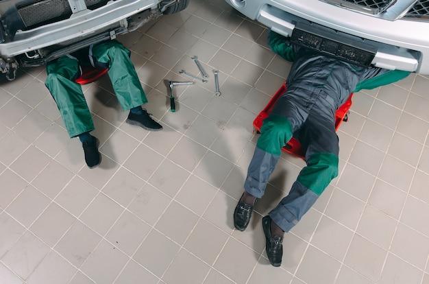 Mecânicos de uniforme deitado e trabalhando embaixo do carro na garagem.