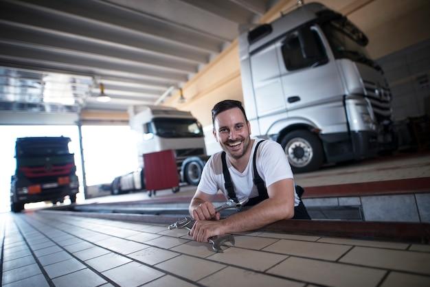 Mecânicos de veículos felizes e sorridentes segurando ferramentas de chave inglesa em oficina de conserto de caminhões