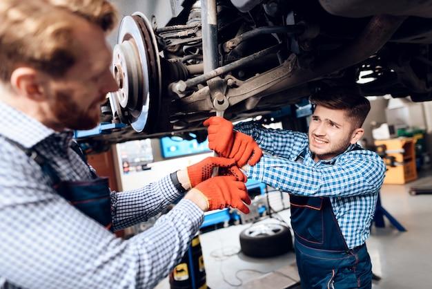Mecânicos novos reparam o cubo automotivo na garagem.