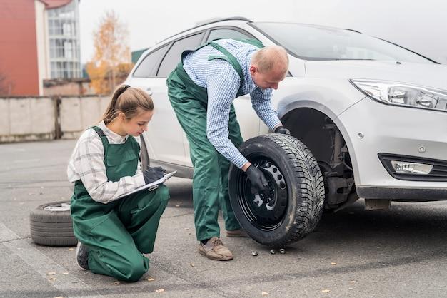 Mecânicos trocando a roda de um carro em serviço
