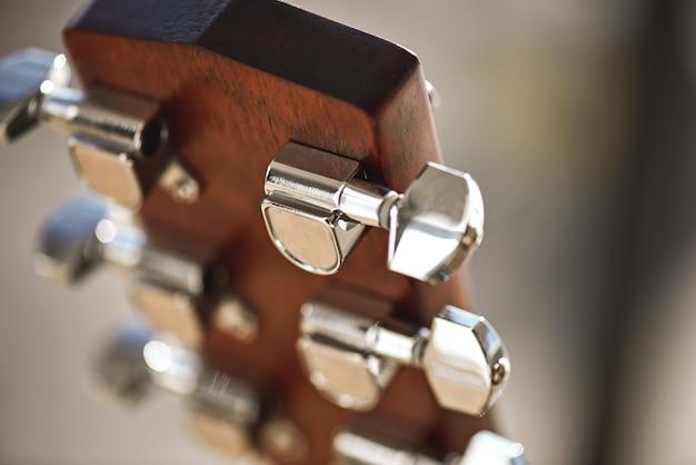 Mecanismo de guitarra. cabeçote de guitarra com foco no mecanismo de enrolamento de cordas: pinos, cordas, abutre. instrumentos musicais. conceito de música.