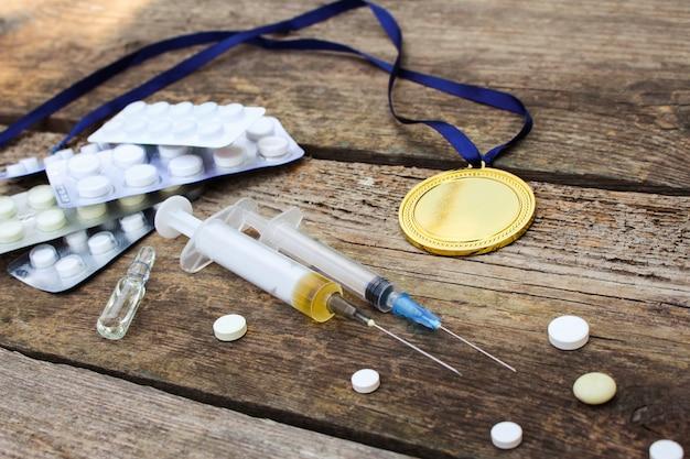 Medalha de esportes e medicamentos em um fundo de madeira.