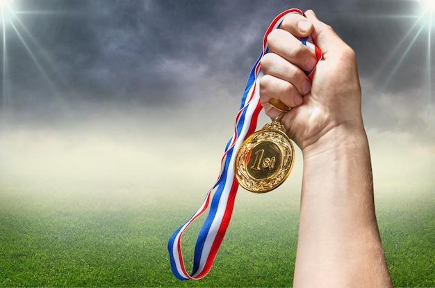 Medalha de ouro com fita na mão no fundo