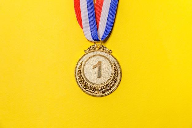 Medalha de troféu de ouro do campeão isolada em fundo amarelo