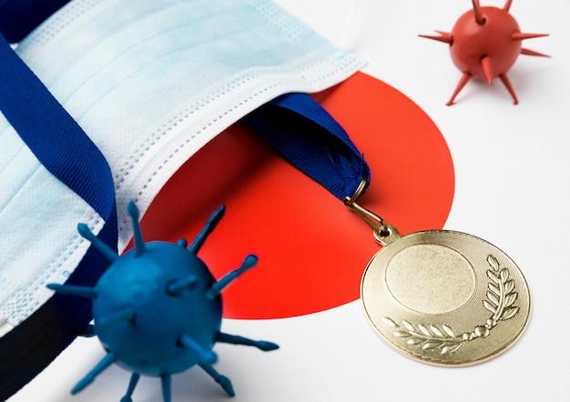 Medalha esportiva ao lado de máscara médica e vírus