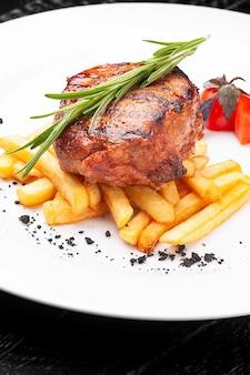 Medalhão de bife com batatas fritas em um prato branco sobre superfície preta