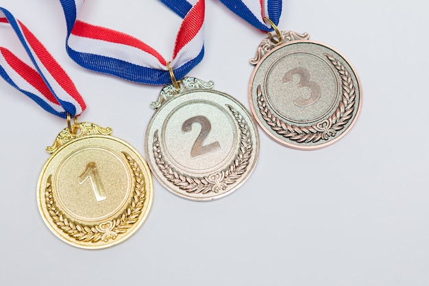 Medalhas de conquistas esportivas de ouro, prata e bronze para o primeiro, segundo e terceiro lugares, em um fundo branco. jogos olímpicos e conceito de esporte.