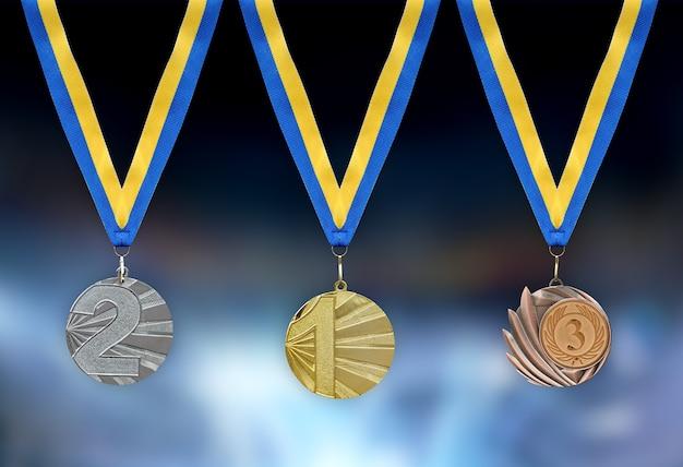 Medalhas de ouro, prata e bronze em primeiro plano com fita amarela azul