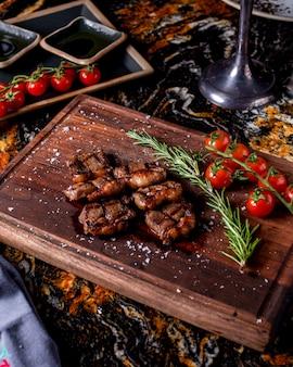Medalhões de carne grelhada servidos com raminho de alecrim e tomate