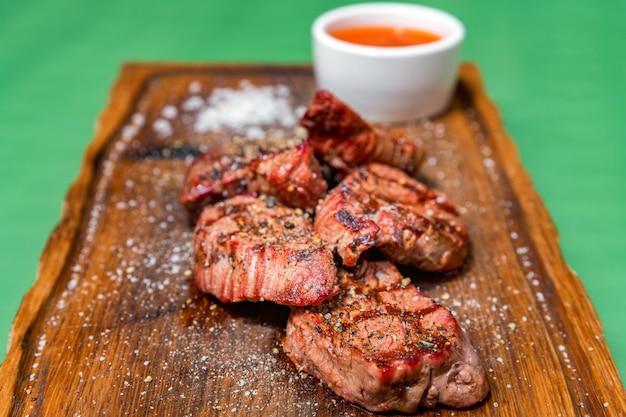 Medalhões de carne grelhada servidos em uma mesa de cozinha de madeira enfeitada com molho