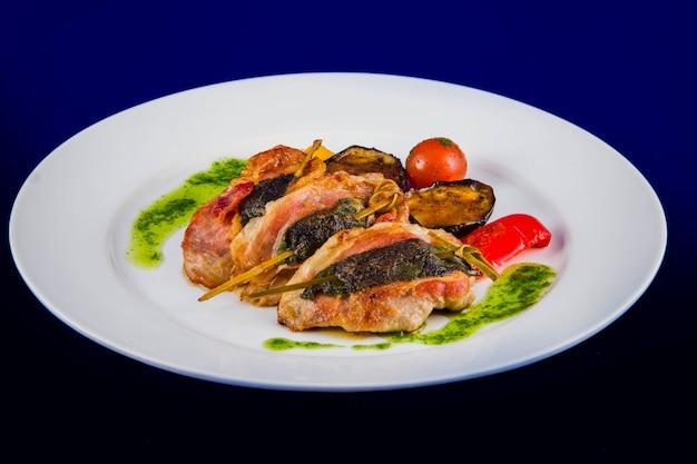 Medalhões de peru recheados com ervas no espeto com legumes grelhados e molho pesto em um prato branco sobre fundo azul.
