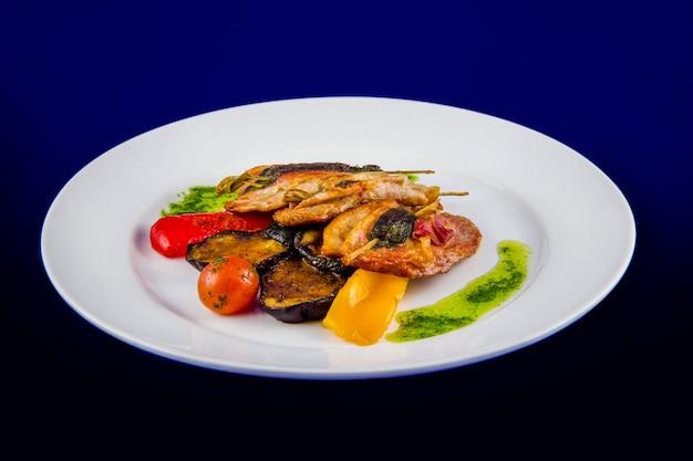 Medalhões de peru recheados com ervas no espeto com legumes grelhados e molho pesto em um prato branco sobre fundo azul. Foto Premium