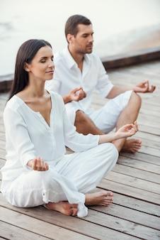 Mediando juntos. vista superior de um lindo casal jovem em roupas brancas, meditando juntos ao ar livre e mantendo os olhos fechados