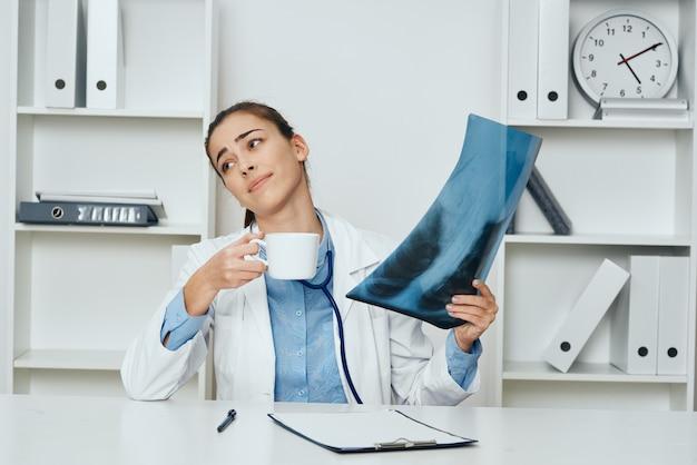 Médica à mesa com um raio-x e uma xícara de café na mão
