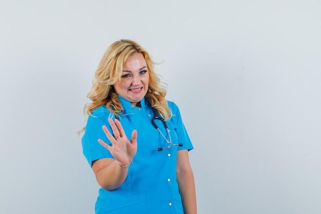 Médica acenando com a mão para saudação em uniforme azul e parece feliz.