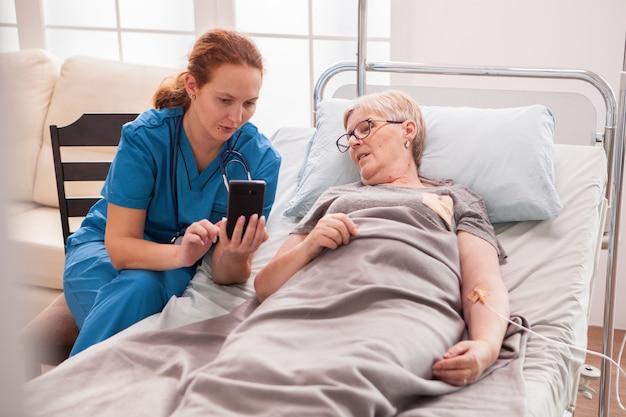 Médica, ajudando a mulher sênior em uma casa de repouso a usar seu telefone.