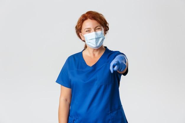 Médica alegre, médica ruiva ou enfermeira de uniforme, máscara facial e luvas, sorrindo amigavelmente e apontando para a câmera