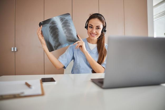 Médica alegre usando laptop para consulta online