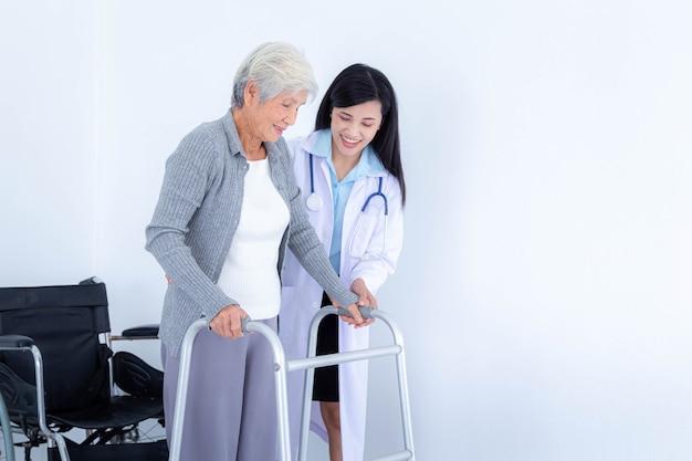 Médica, apoiando a mulher sênior usando o andador. cuidado do paciente idoso e cuidados de saúde, conceito médico.